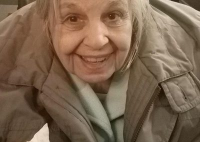 elderly woman in gray coat smiles to camera