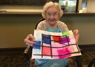 elderly woman holds up her painting