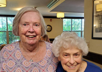 two women in blouses smile for camera