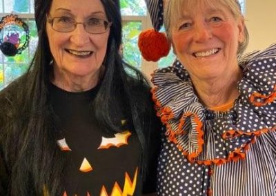two women pose in Halloween costumes