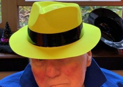 man poses in yellow fedora