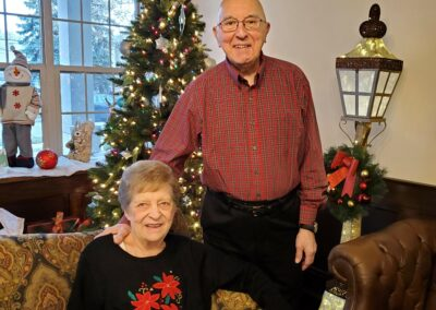 elderly couple pose in front of Christmas tree