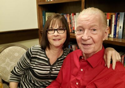 woman with glasses poses with man in red shirt