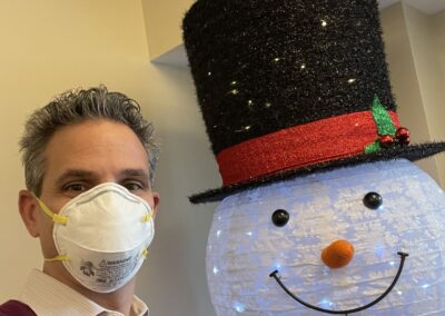 man in mask poses next to snowman decoration