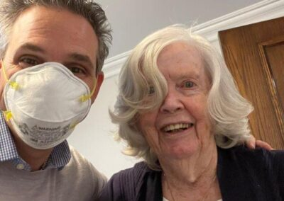 man in mask poses next to elderly woman