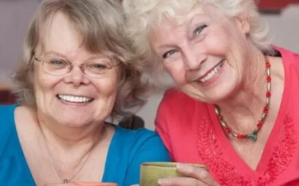 two elderly women hold coffee mugs and smile