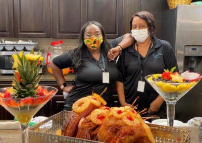 women in masks pose next to food buffet
