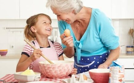 elderly woman and young girl baking together